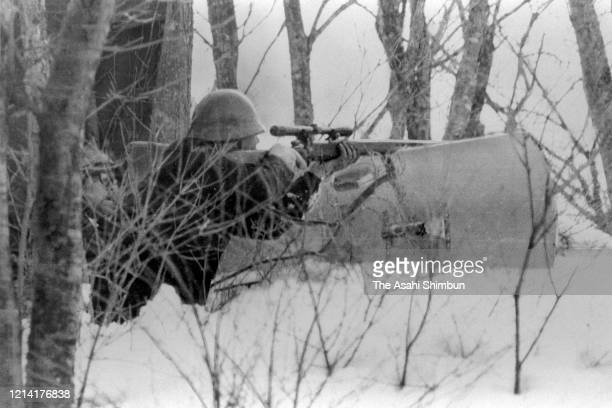 A riot police sniper takes aim on the Asama Sanso lodge where the United Red Army members take a hostage on February 23 1972 in Karuizawa Nagano Japan