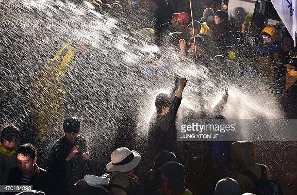 Riot police spray South Korean protestors with a water cannon in front of the Gwanghwamun the main gate to the Gyeongbok Palace during a rally to...