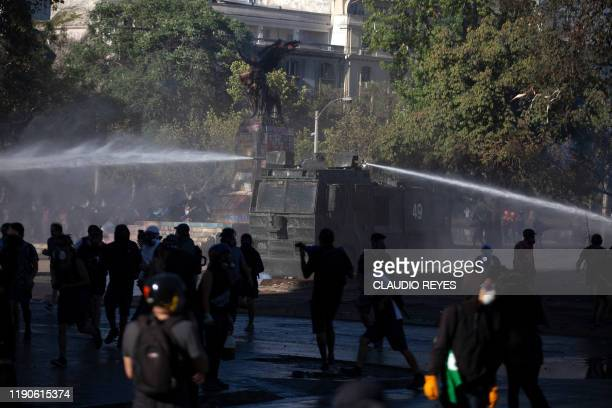 TOPSHOT Riot police spray water to disperse demonstrators during a protest against Chilean President Sebastian Pinera's government in Santiago on...
