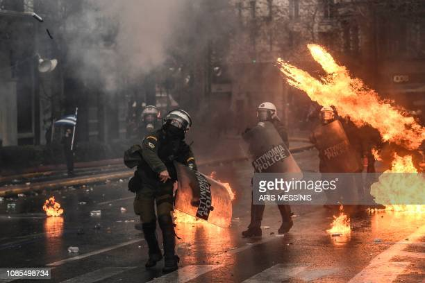 Riot police stand amid fire during a demonstration against the agreement with Skopje to rename neighbouring country Macedonia as the Republic of...