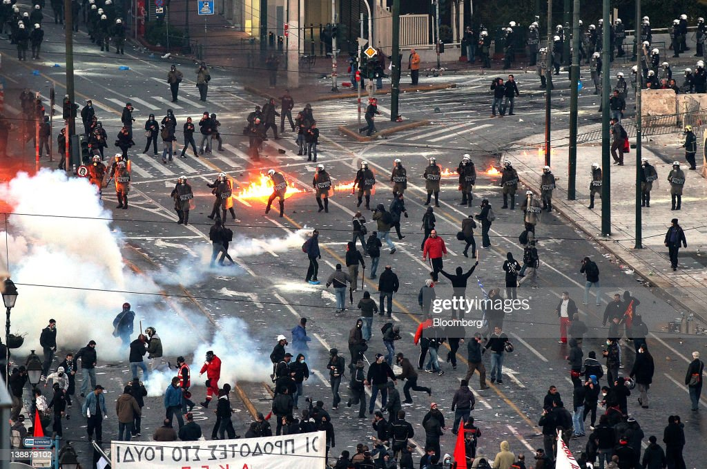 Riot police stand amongst tear gas and petrol bombs as they clash with protestors outside the Greek parliament in Athens, Greece, on Sunday, Feb. 12, 2012. Greek Prime Minister Lucas Papademos won parliamentary approval for austerity measures to secure an international bailout after rioters protesting the measures battled police and set fire to buildings in downtown Athens. Photographer: Simon Dawson/Bloomberg via Getty Images