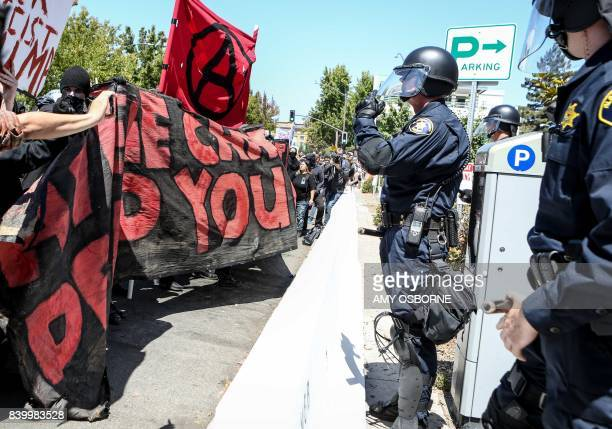 Riot police stand before Antifa members and counter protesters during a rightwing No To Marxism rally on August 27 2017 at Martin Luther King Jr Park...