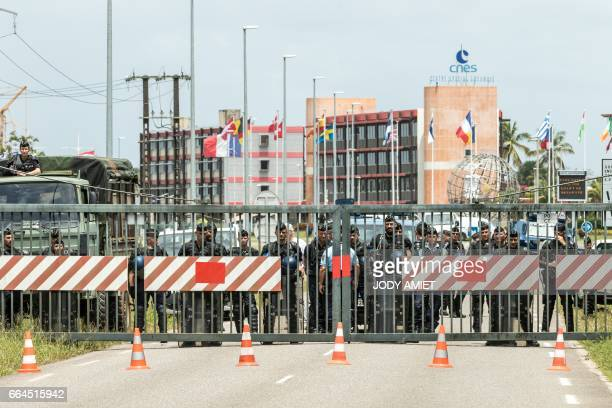 Riot police stand behind a bareer at the entrance of Kourou space center as demonstrators protest over security and the state of the economy on April...