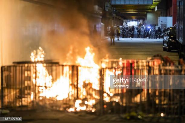 Riot police stand behind a barricade set on fire by demonstrators during a protest in the Sheung Wan district of Hong Kong China on Sunday July 21...