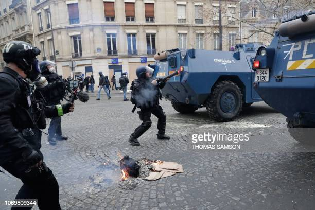 Riot police stand behind Gendarmerie armored vehicles during a protest of yellow vests against rising costs of living on December 8 2018 in Paris...