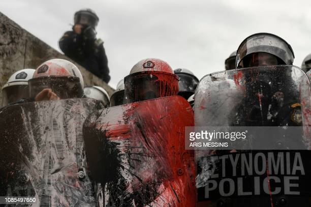 Riot police stand behind stained shields during a demonstration against the agreement with Skopje to rename neighbouring country Macedonia as the...
