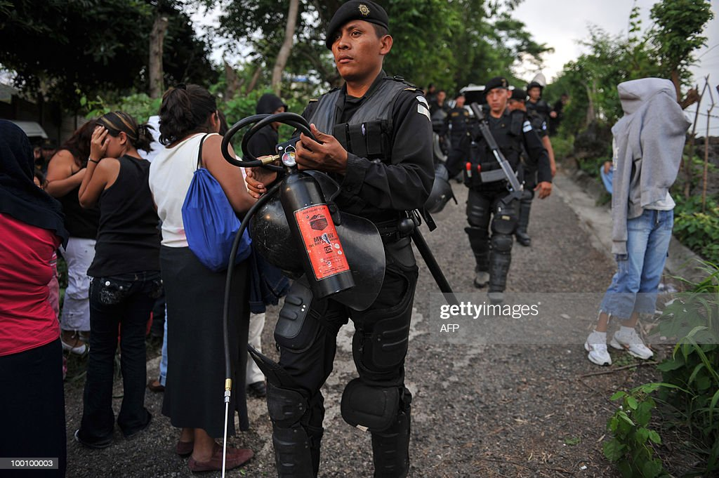 Riot police stand by along relatives of inmates of 'El Boqueron' maximum security prison May 20, 2010, in Santa Rosa, some 90 km east of Guatemala City. The warden and three guards were taken hostage on Thursday by prisoners belonging to the infamous Mara Salvatrucha gang, police said. AFP PHOTO/Johan ORDONEZ.