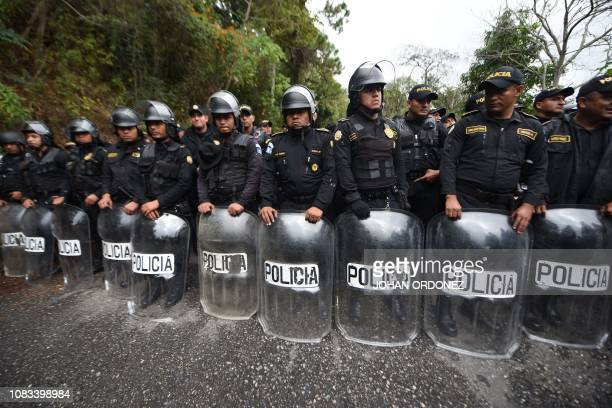 TOPSHOT Riot police stand by as Honduran migrants continue to head to the United States with a second caravan after reaching an agreement with the...