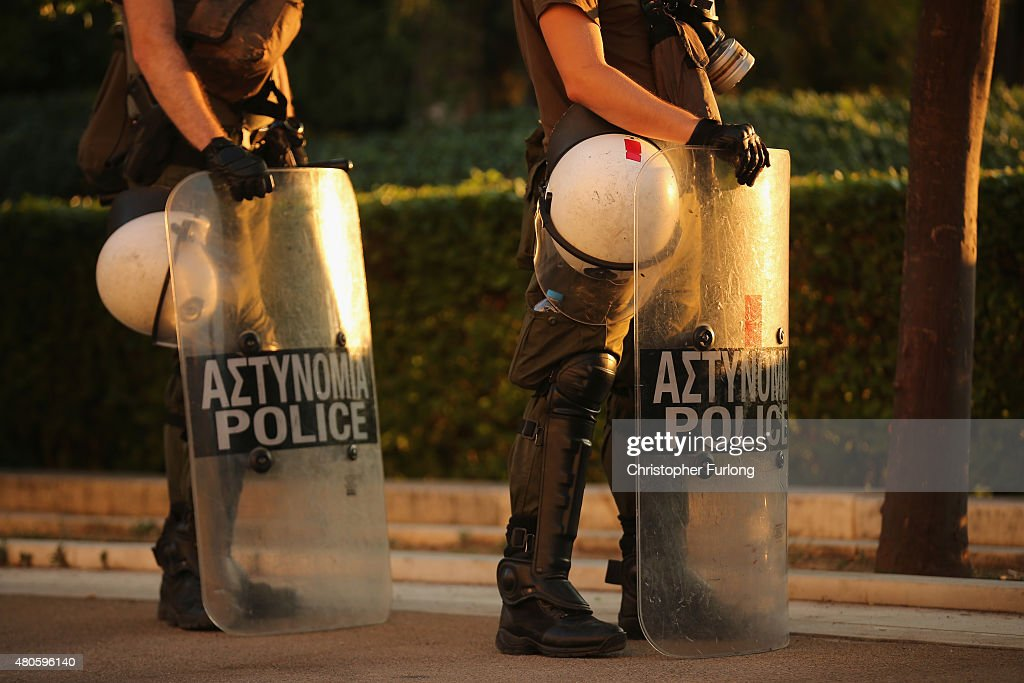 Riot police stand by as protesters gather outside the Greek parliament to demonstrate against austerity after an agreement for a third bailout with eurozone leaders on July 13, 2015 in Athens, Greece. The bailout is conditional on Greece passing agreed reforms in parliament by Wednesday which includes streamlining pensions and rasing more raise tax revenue.
