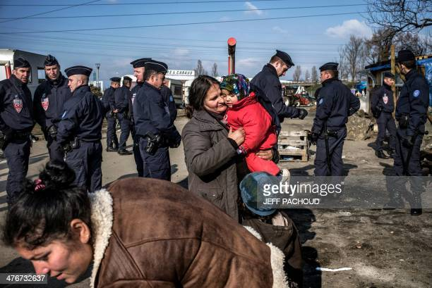 Riot Police stand by People from the Roma community as they are being evicted from their makeshift camp on March 5 2014 in Lyon AFP PHOTO / JEFF...