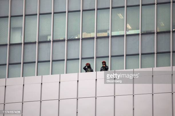 Riot police stand guard and watch from government offices during a protest in Admiralty district of Hong Kong China on Sunday Oct 6 2019 Violence...