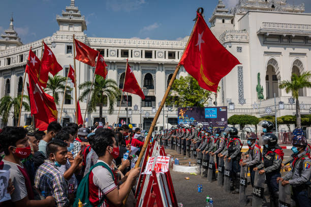 Riot police stand guard as protesters approach a barricade on February 07, 2021 in Yangon, Myanmar. Some internet services were restored in Myanmar...