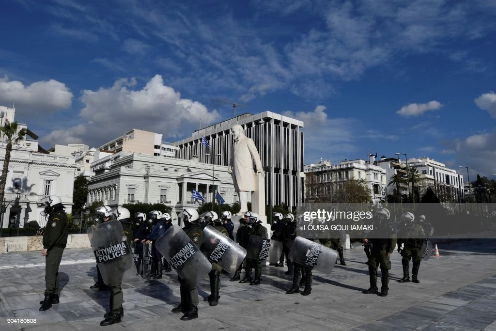 Riot police stand guard in front of the parliament building in Athens on January 12, 2018, during a demonstration against changes to a 36-year-old industrial action law demanded by the country's creditors . /