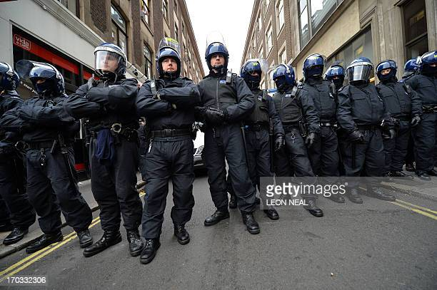 Riot police stand guard near a building thought to be an anticapitalist squat in central London on June 11 as few hunderd protesters took to the...