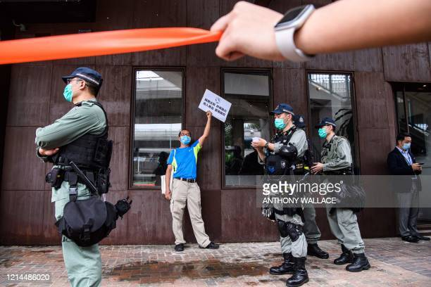 Riot police stand guard near a pro-democracy protester , who was stopped with others before being fined for breaking government-imposed social...