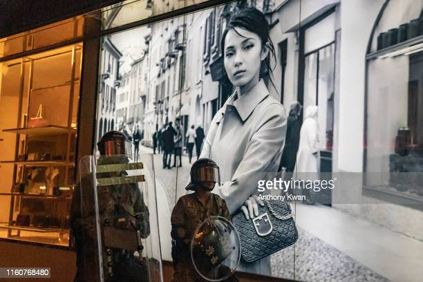 Riot police stand guard next to a fashion ads after a clearing at a demonstration in Tsim Sha Tsui on August 10 2019 in Hong Kong China Prodemocracy...