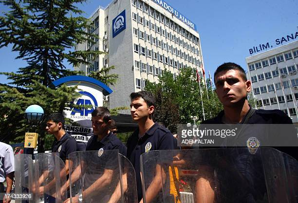 Riot police stand guard on July 24 2013 outside the headquarters of Anadolu news agency in Ankara as a group of journalists and members of the...