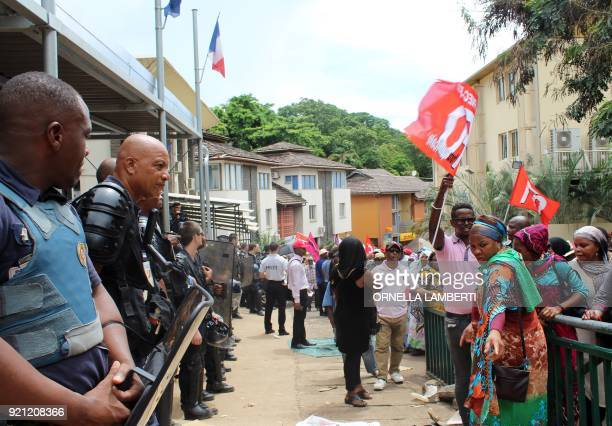 Riot Police stand guard outside the Prefercture building as people display banners during a demonstration in Mamoudzou in the French overseas...