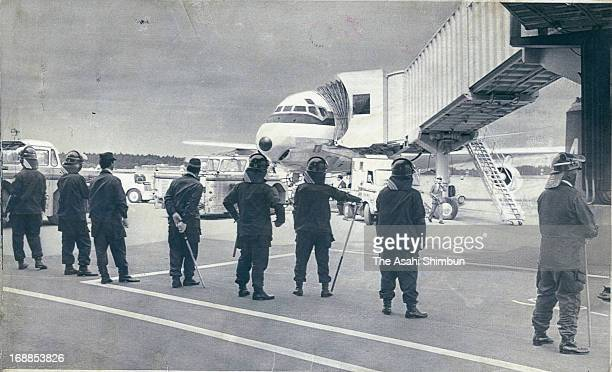 Riot police stand guard the first flight Japan Airlines 947 takeoff from the newly opened New Tokyo International Airport on May 22 1978 in Narita...