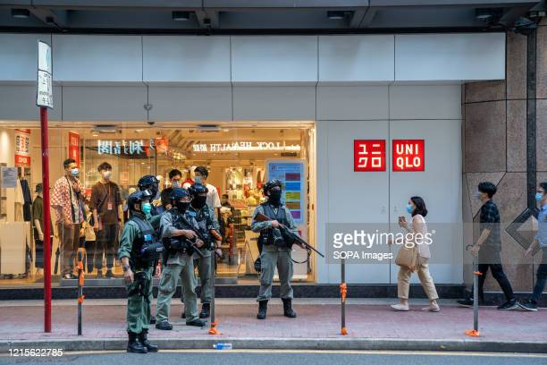 Riot police stand guard with their weapons outside a Uni Qlo clothing store in Causeway Bay as demonstrators are anticipated to gather in the area to...
