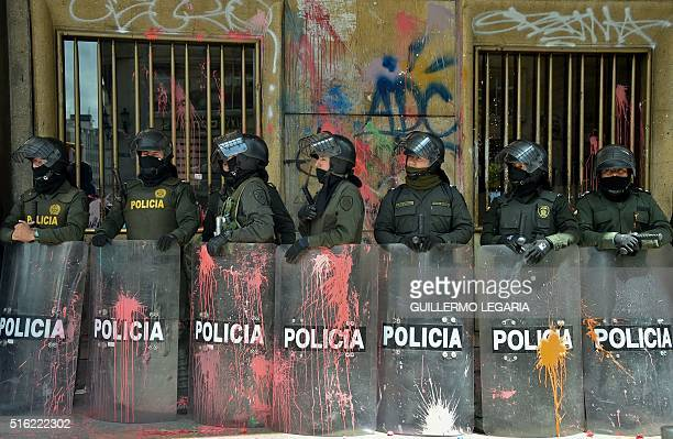 TOPSHOT Riot police stand in a line with their shields stained with paint during a protest in Bogota on March 17 2016 as part of a national strike...
