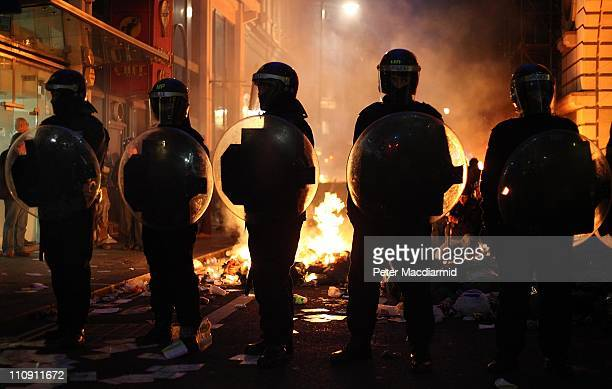 Riot police stand in front of a burning barricade in Jermyn Street during clashes with protesters after a march in protest against government cuts on...