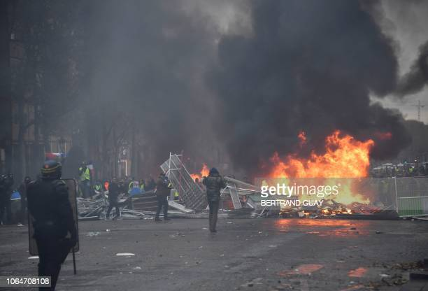 TOPSHOT Riot police stand in front of a fire near the place de la Concorde in Paris on November 24 2018 during a protest of Yellow vest against...