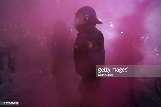 Riot police stand in purple smoke during scattered leftwing protests in Kreuzberg district on May Day during the novel coronavirus crisis on May 1...