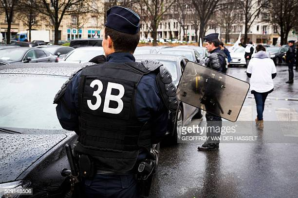 A riot police stand next to cars on the Place de la Nation in Paris on February 9 during a demonstration by nonlicensed private hire cab drivers...