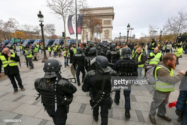 Riot police stand next to protestors near the ChampsElysees avenue in Paris on December 8 2018 during a quotyellow vestquot protest against rising...