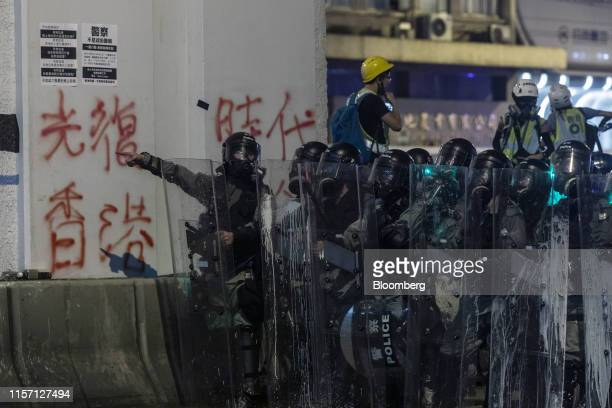 Riot police stand off against demonstrators during a protest in the Sheung Wan district of Hong Kong China on Sunday July 21 2019 Tens of thousands...