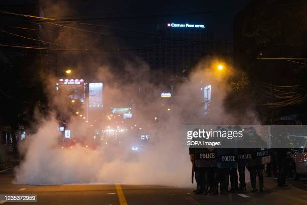 Riot police stand on guard in the cloud of tear gas on Rajavithi road during the demonstration. The pro-democracy protesters gathered at democracy...