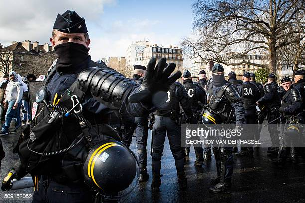 Riot police stand on the Place de la Nation in Paris on February 9 during a demonstration by nonlicensed private hire cab drivers known in France as...
