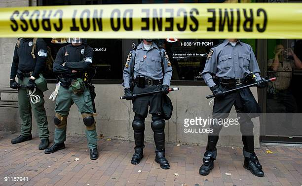 Riot police stand on the sidewalk as thousands of demonstrators march through downtown Pittsburgh Pennsylvania September 25 to protest the G20...