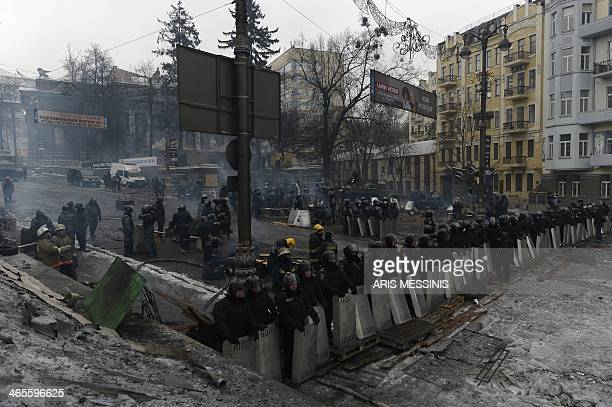 Riot police stand opposite an antigovernment road block in Kiev on January 28 2014 Ukrainian lawmakers scrapped on January 28 draconian antiprotest...