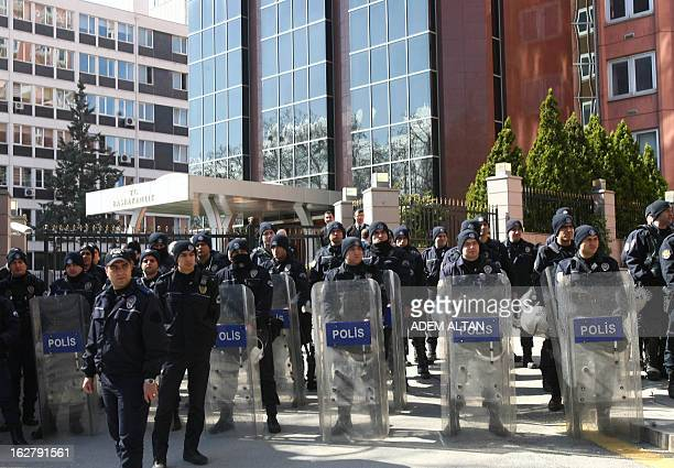 Riot police stand outside the Prime Ministry building as members of all Turkish civil servant unions walk to protest against the government's economy...