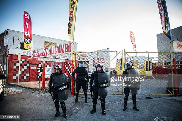 Riot police stand watch over a tire shop during protests near the CVS pharmacy that was burned to the ground yesterday during rioting after the...