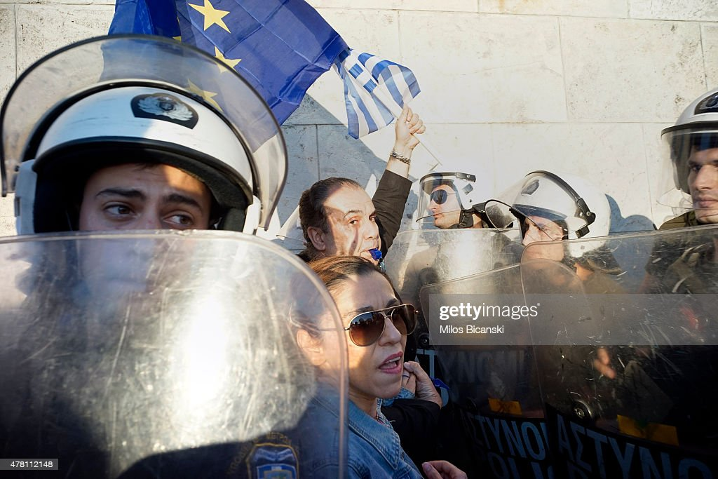 Riot police stand with shields as pro-Euro protesters take part in a rally in front of the Parliament on June 22. 2015 in Athens, Greece. Thousends of people attended the rally in support of Greece remaining in the European Union. The Eurozone's 19 national leaders held an emergency summit in Brussels to discuss the crisis and welcomed new proposals from the Greek government after talks today to haul Athens back from the brink of bankruptcy.