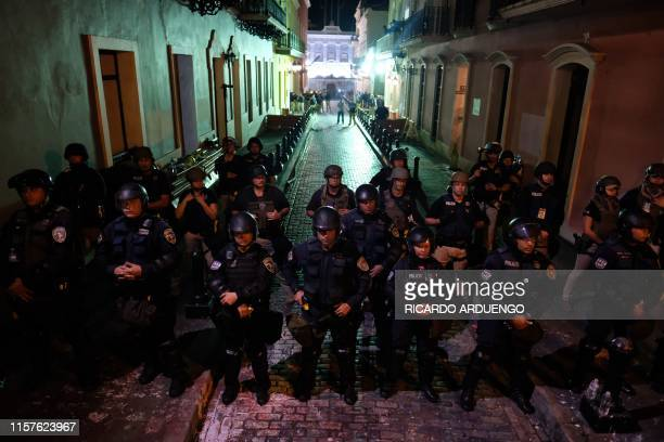 Riot police stands in formation in front of the Puerto Rico's governor mansion known as La Fortaleza in San Juan on July 24 2019 Puerto Rico's...