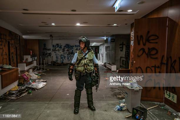 A riot police stands near graffiti inside the Legislative Council building after it was damaged by demonstrators during a protest on July 2 2019 in...