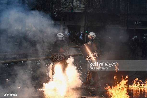 A riot police stands on fire during a demonstration against the agreement with Skopje to rename neighbouring country Macedonia as the Republic of...
