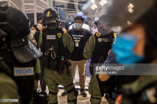 TOPSHOT Riot police stop and search a man in a shopping mall after prostesters gathered to mark one year since a group of whiteclad men attacked...