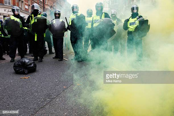 Riot police surrounded by yellow smoke from a smoke bomb stand their ground after a clash on a street in Mayfair Anti capitalists / anarchists go on...