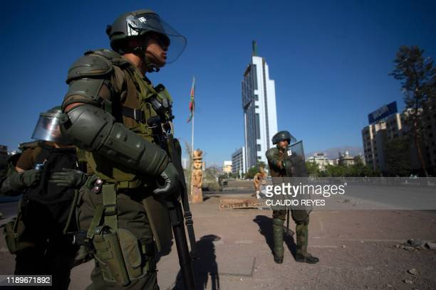 Riot police take position during a protest against Chilean President Sebastian Pinera's government in Santiago on December 20 2019 Pinera promised...