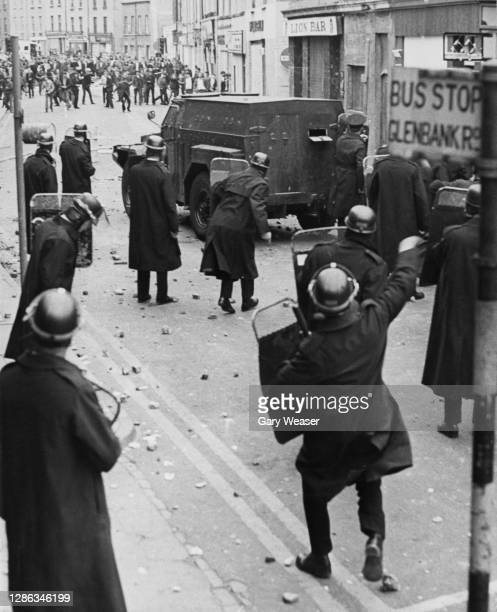 Riot police take shelter behind their shields and an armoured van as trouble flared following the annual Apprentice Boys parade through the streets...
