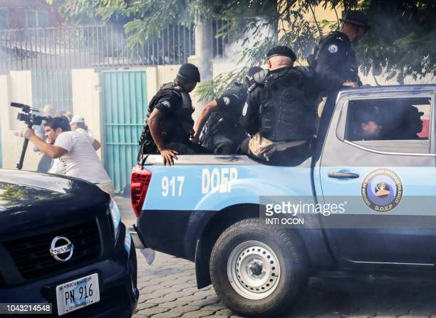 Riot police throw stun bombs to journalists during a protest against Nicaraguan President Daniel Ortega's government in Managua on september 29 2018...