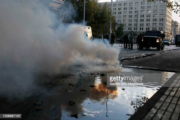 Riot police throw tear gas bombs to demosntrators during protests against the government of Sebastián Piñera on its second anniversary on March 11...