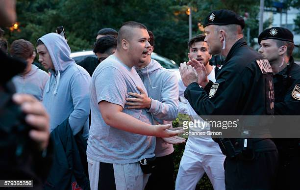 Riot police try to calm down teenage mourners shouting muslim slogans near the crime scene at OEZ shopping center the day after a shooting spree left...