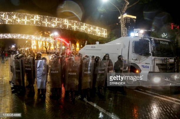 Riot police units stand guard during clashes with protesters in front of the Interior Ministry building during a demonstration in Tirana on December...
