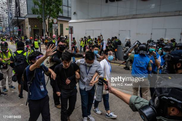 Riot police use pepper spray during a protest against a planned national security law in the Causeway Bay district on May 24, 2020 in Hong Kong,...